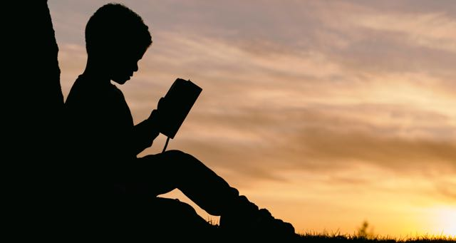 silhouette of a boy reading a book at sunset