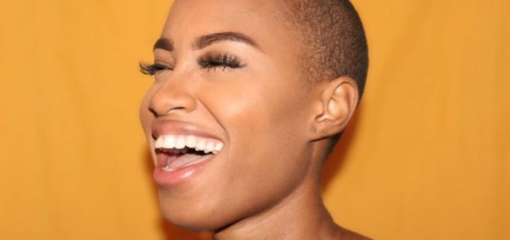 woman on yellow background laughing