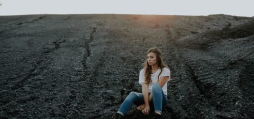 a girl sitting alone in the dirt
