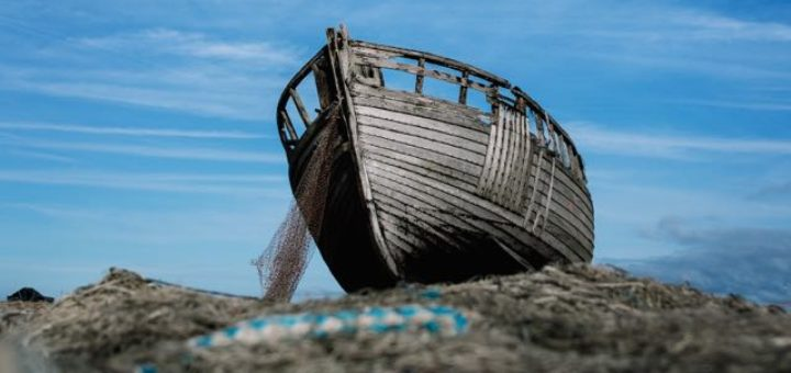 old boat with finish net on the shore