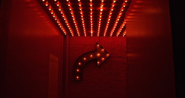 red-lit hallway with a red arrow