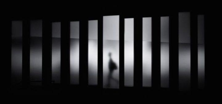 abstract man walking behind a tinted glass wall