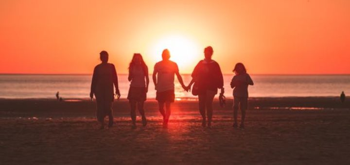 group of people walking on the beach at sundown