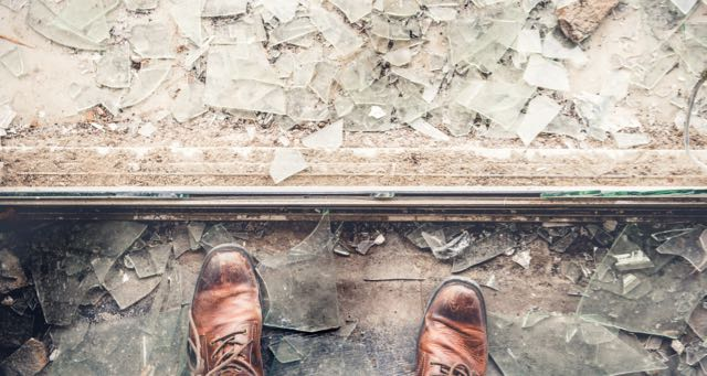 man stepping on broken glass