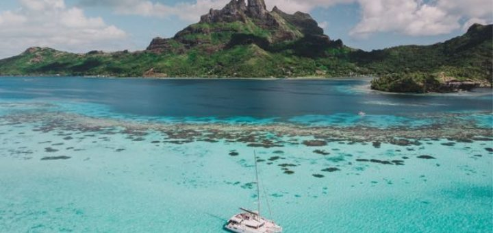 boat anchored by a shallow coral reef