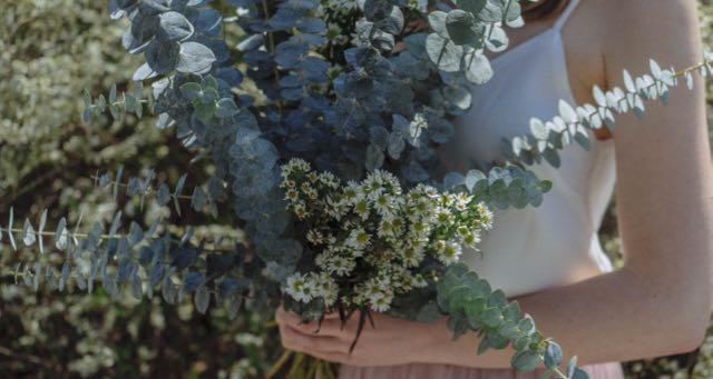 girl in white dress holding green flowers