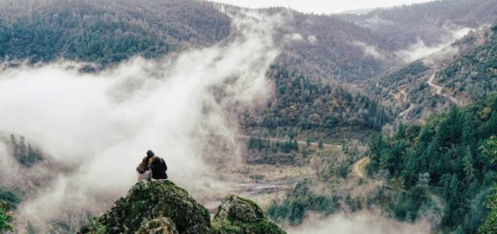 couple sitting on a rock overlooking a foggy valley