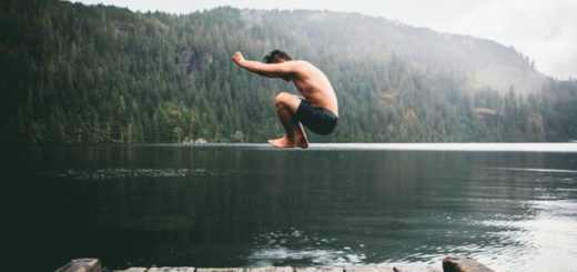 a boy jumping in a lake from a pier
