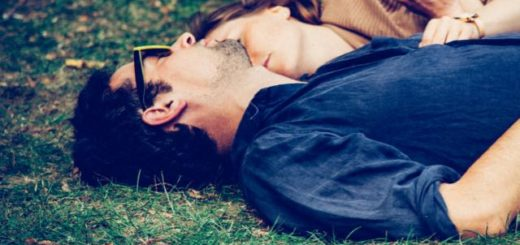 couple laying on the grass in a park