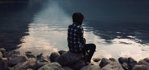 girl sitting on a rock overlooking a lake