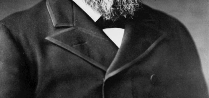 black and white photo of a man with beard in black trench coat