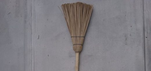 broom against a gray wall haibun