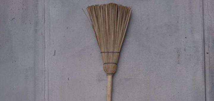 broom against a gray wall haibun