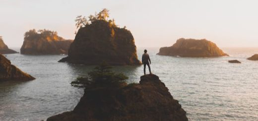man standing on a cliff overlooking island in the ocean