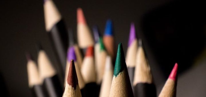 color pencils pointing up on a desk